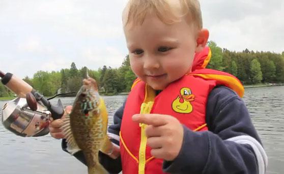 petit garçon pêche son premier poisson