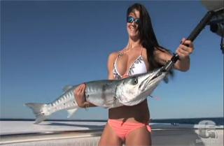 jolie fille qui peche un barracuda
