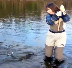 une femme à la pêche terrorisée par le poisson qu'elle vient de prendre