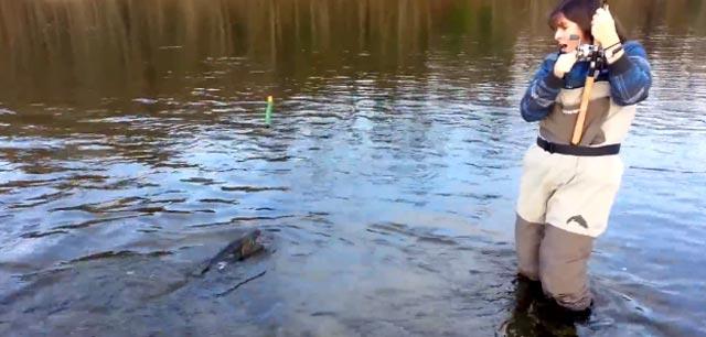 pêcheuse effrayée par le poisson au bout de sa ligne
