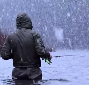 fly fisherman under the snow in winter